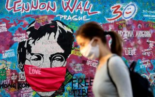 A woman wearing a face mask walks past the legendary graffiti-covered John Lennon Wall as the spread of the coronavirus disease (COVID-19) continues in Prague, Czech Republic, April 6, 2020.  REUTERS/David W Cerny