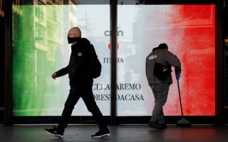 A man wearing a protective mask walks past a banner with the Italian flag placed behind a window of the Termini train station, as the spread of the coronavirus disease (COVID-19) continues, in Rome, Italy April 7, 2020. REUTERS/Remo Casilli