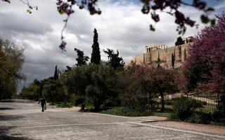 A man carrying a bag of goods walks on an empty pedestrian street under the Acropolis hill, during the coronavirus disease (COVID-19) outbreak, in Athens, Greece, April 7, 2020. REUTERS/Alkis Konstantinidis