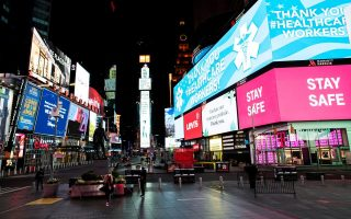 People walk in Times Square, Manhattan while some screens are seen illuminated in blue as part of the