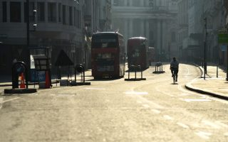 London buses and a cyclist are seen in central London as the spread of the coronavirus disease (COVID-19) continues, London, Britain, April 10, 2020. REUTERS/Dylan Martinez