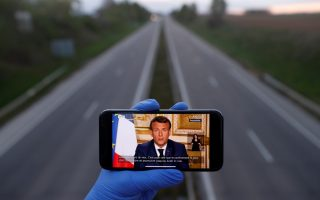 A mobile phone showing French President Emmanuel Macron, as he addresses the nation about the coronavirus disease (COVID-19) outbreak, is displayed for a photo in front of an almost empty motorway in Strasbourg, France, April 13, 2020. REUTERS/Christian Hartmann