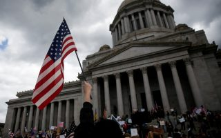 A person waves an American flag during a protest against the state's extended stay-at-home order to help slow the spread of the coronavirus disease (COVID-19) at the Capitol building in Olympia, Washington, U.S. April 19, 2020. REUTERS/Lindsey Wasson