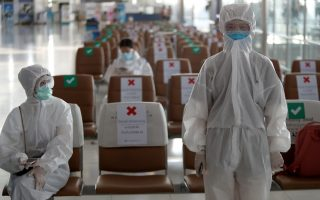 Chinese students living in Thailand wear protective suits as a measure of protection against the coronavirus disease (COVID-19) at the Suvarnabhumi Airport before boarding a repatriation flight, in Bangkok, Thailand April 21, 2020. REUTERS/Jorge Silva