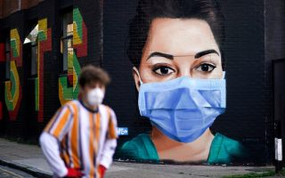 A man wearing a protective mask walks past a mural depicting a nurse in Shoreditch, amid the coronavirus disease (COVID-19) outbreak, in London, Britain April 21, 2020. REUTERS/Henry Nicholls     TPX IMAGES OF THE DAY
