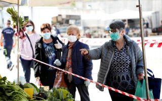 People wearing protective face masks queue in line at an open-air food market that has been reopened, during the coronavirus disease (COVID-19) outbreak in Cisternino, Italy, April 27, 2020. REUTERS/Alessandro Garofalo