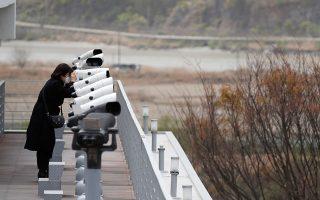 Επισκέπτης στο περίπτερο Ιμτζινγκάκ στη νοτιοκορεατική πλευρά κοιτάζει με τα κιάλια προς τα βόρεια.