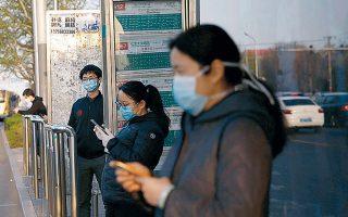 Πολίτες φορώντας μάσκες περιμένουν σε στάση λεωφορείων στο Πεκίνο.