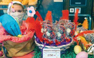 Φορώντας προστατευτική μάσκα, μια εργαζόμενη τοποθετεί παραδοσιακά πασχαλινά είδη στη βιτρίνα φούρνου της Σαραγόσα, στη βόρεια Ισπανία.