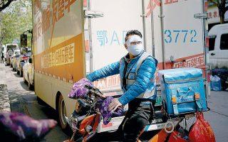 Υπάλληλος εταιρείας ντελίβερι σε συνοικία της πόλης Γουχάν, στην Κίνα, μετά την άρση της καραντίνας.