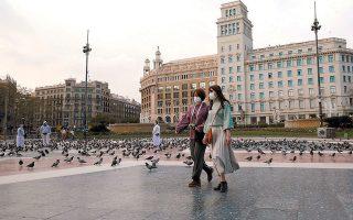 Γυναίκες με προστατευτικές μάσκες διασχίζουν την έρημη πλατεία Καταλωνίας, στο κέντρο της Βαρκελώνης.
