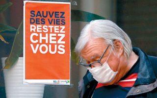 Ανδρας που φοράει προστατευτική μάσκα περνάει μπροστά από αφίσα με σύνθημα «Σώστε ζωές, μείνετε σπίτι», στο Φοντενέ-σου-Μπουά της Γαλλίας.