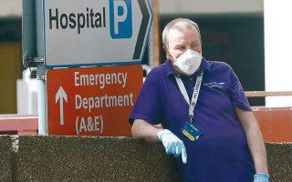 Ανδρας με προστατευτική μάσκα και γάντια στέκεται έξω από το νοσοκομείο Σεν Τόμας, στο Λονδίνο, όπου έχει εισαχθεί ο Μπ. Τζόνσον.