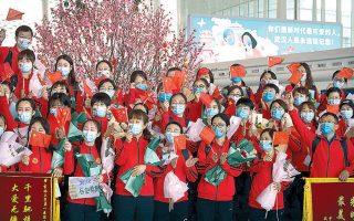 Με κινεζικές σημαίες αποχαιρετούν τη Γουχάν γιατροί και νοσηλευτές από την επαρχία Γιλίν, που επιστρέφουν στα σπίτια τους έπειτα από 11 εβδομάδες.