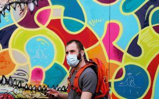 Ανδρας με μάσκα βαδίζει μπροστά από γκράφιτι, στο Παρίσι.