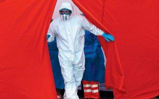 Νοσηλευτής ετοιμάζεται να διενεργήσει τεστ για κορωνοϊό στο νεοπαγές κέντρο drive-in της Δρέσδης.