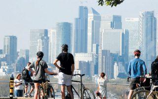 Περαστικοί θαυμάζουν τη θέα από το πάρκο Γκρίνουιτς του Λονδίνου.