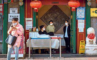 Υπάλληλοι φορούν μάσκες για να αποτρέψουν τη διασπορά της COVID-19, στην είσοδο εστιατορίου στο Πεκίνο.