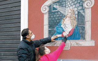 Μπαμπάς και κόρη με μάσκες αγγίζουν την εικόνα της Σάντα Αγκάθα, προστάτιδος της πόλης Κατάνια στην Ιταλία.