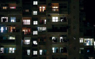 Σιλουέτες ανθρώπων αχνοφαίνονται στα μπαλκόνια πολυκατοικίας σε προάστιο στο Νέο Δελχί, καθώς συνεχίζονται τα περιοριστικά μέτρα στην ινδική πρωτεύουσα.
