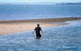 Ανδρας ψαρεύει στα ρηχά στο Μπρισμπέιν της Αυστραλίας. Η επιβίωση του ιού στα λύματα ήταν ένας από τους λόγους που ώθησαν ορισμένους ειδικούς να ζητήσουν απαγόρευση της κολύμβησης.