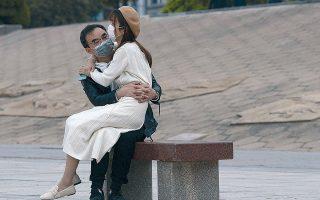 Νεαρό ζευγάρι κάθεται μαζί σε παγκάκι της Γουχάν στην επαρχία Χουμπέι της Κίνας.