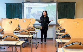 Καθηγήτρια γεωγραφίας στέκεται μπροστά σε άδεια σχολική αίθουσα στο Χάναου της Γερμανίας.