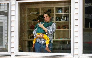 Μια έγκυος γυναίκα κρατάει αγκαλιά τον γιο της όσο παραμένει σε καραντίνα στο Κέιπ Ελίζαμπεθ του Μέιν, στις ΗΠΑ.