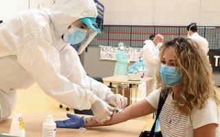 Γυναίκα υποβάλλεται σε τεστ που οργάνωσε η κοινότητα του Τσιζλιάνο στη διάρκεια των περιοριστικών μέτρων στο Μιλάνο της Ιταλίας.