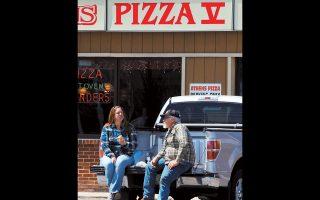 Ενα ζευγάρι τρώει το γεύμα του στο πάρκινγκ, καθώς το εστιατόριο στο Κιν του Νιου Χαμσάιρ των ΗΠΑ προσφέρει φαγητό μόνο για διανομή.