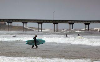 Σέρφερ με τη σανίδα του στα κύματα της παραλίας του Σαν Ντιέγκο.