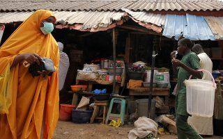 Υπαίθρια αγορά στην πόλη Αμπούτζα της Νιγηρίας λίγο πριν επιβληθεί στη χώρα καραντίνα. Πολλοί κάτοικοι, αν δεν βγουν από το σπίτι τους κάθε μέρα για να δουλέψουν, δεν έχουν εισόδημα ούτε για τρόφιμα. Ο κίνδυνος επισιτιστικής κρίσης είναι μεγάλος. EPA / GEORGE ESIRI