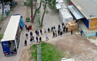 Μεταφορά κιβωτίων με πρώτες ύλες για το μαγείρεμα φαγητού στη δομή φιλοξενίας προσφύγων στη Ριτσώνα, η οποία έχει μπει σε καραντίνα 14 ημερών από την περασμένη Πέμπτη. EPA / ANDREAS TSAKNARIDIS