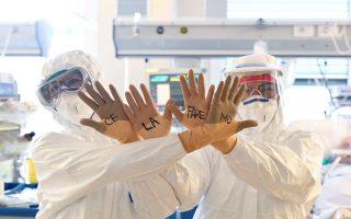 Μέλη του ιατρικού προσωπικού σε νοσοκομείο της Ιταλίας υψώνουν τα χέρια τους για να φανεί το μήνυμα «Ce la faremo» («Θα τα καταφέρουμε») που είναι γραμμένο πάνω στα προστατευτικά γάντια τους