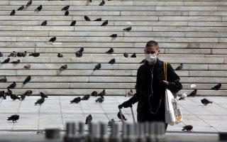 Μία γυναίκα που φορά προστατευτική μάσκα περπατά στην άδεια πλατεία Συντάγματος, λόγω των μέτρων απαγόρευσης κυκλοφορίας για την αποφυγή εξάπλωσης του κορονοϊού, Τρίτη 7 Απριλίου 2020. ΑΠΕ-ΜΠΕ/ΑΠΕ-ΜΠΕ/Αλέξανδρος Μπελτές