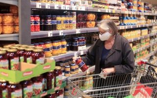 FILE PHOTO: An elderly woman wearing a face mask shops in a supermarket, after the federal state of North Rhine-Westphalia decided to make wearing protective masks obligatory in shops and public transportation to fight the spread of the coronavirus disease (COVID-19), in Bad Honnef near Bonn,  Germany, April 27, 2020. REUTERS/Wolfgang Rattay/File Photo