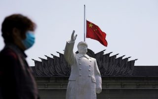 FILE PHOTO: The Chinese national flag flies at half-mast behind a statue of late Chinese chairman Mao Zedong in Wuhan, Hubei province, as China holds a national mourning for those who died of the coronavirus disease (COVID-19), on the Qingming tomb-sweeping festival, April 4, 2020. REUTERS/Aly Song/File Photo