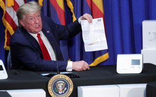 President Donald Trump holds up a chart on global coronavirus disease (COVID-19) testing as he sits in front of coronavirus testing machines and their boxes that he brought with him from Washington for his visit to a Honeywell facility manufacturing protective face masks in Phoenix, Arizona, U.S., May 5, 2020. REUTERS/Tom Brenner