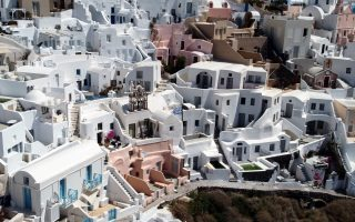 A Greek national flag flutters among houses in Oia, following the coronavirus disease (COVID-19) outbreak, on the island of Santorini, Greece, May 8, 2020. Picture taken with a drone. REUTERS/Alkis Konstantinidis