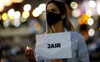 Νοσοκόμα διαδηλώνει στη Μπραζίλια κρατώντας πλακάτ που αναγράφει το όνομα συναδέλφου της που πέθανε από τον κορωνοϊό. Reuters/Adriano Machado