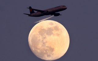 FILE PHOTO: An airplane of German air carrier Lufthansa passes the moon over Frankfurt, Germany, April 9, 2017.  REUTERS/Kai Pfaffenbach/File Photo