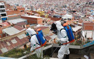 Συνεργείο του δήμου απολυμαίνει σε φτωχογειτονιά της Λα Πας, πρωτεύουσας της Βολιβίας, όπου η πανδημία βρίσκεται σε έξαρση (φωτ. A.P.).