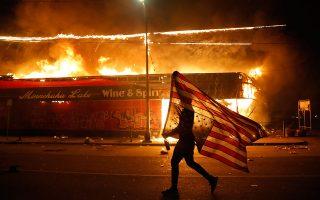 Διαδηλωτής κρατάει την αμερικανική σημαία ανάποδα, μπροστά από φλεγόμενο κτίριο, στη Μινεάπολη. (A.P. Photo / Julio Cortez)