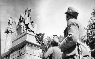 Γερμανοί στρατιώτες, τον Ιούνιο του 1941, κοιτάζουν το άγαλμα του Σωκράτη, έργο του γλύπτη Λεωνίδα Δρόση, στον προαύλιο χώρο της Ακαδημίας Αθηνών. A.P.