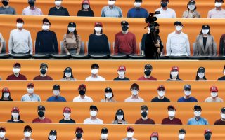 A TV camera man walks in rows of seats covering banners with pictures of fans before the start of regular season baseball game between Hanwha Eagles and SK Wyverns in Incheon, South Korea, Tuesday, May 5, 2020. South Korea's professional baseball league start its new season on May 5, initially without fans, following a postponement over the coronavirus. (AP Photo/Lee Jin-man)