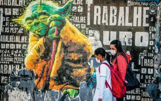 Δύο νεαρές Βραζιλιάνες περπατούν σε δρόμο του Σάο Πάολο φορώντας προστατευτικές μάσκες. Δυστυχώς, όμως, ο μισός πληθυσμός της χώρας αγνοεί τις οδηγίες των ειδικών και ακολουθεί τις «συμβουλές» του Μπολσονάρο. EPA / FERNANDO BIZERRA