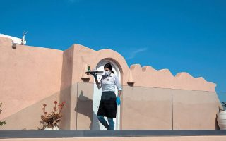 Υπάλληλος ξενοδοχείου με μάσκα και γάντια, στο Μεγαλοχώρι της Σαντορίνης, την εβδομάδα που μας πέρασε. REUTERS / ALKIS KONSTANTINIDIS