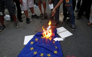 Protesters burn an EU flag during an anti-bailout protest outside of Cyprus' parliament in Nicosia, Tuesday, April 30, 2013. Cyprus' lawmakers are voting Tuesday on a multi-billion bailout agreement aimed at preventing the country from going bankrupt. The 56-seat parliament is expected to narrowly approve the 23 billion-euro ($30 billion) deal that the country struck with its euro partners and the International Monetary Fund last month. (AP Photo/Petros Karadjias)