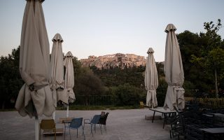 Umbrellas and chairs of a closed cafe are seen in Thissio district with the Acropolis hill seen in the background, following the coronavirus disease (COVID-19) outbreak, in Athens, Greece, April 28, 2020. Picture taken April 28, 2020. REUTERS/Alkis Konstantinidis