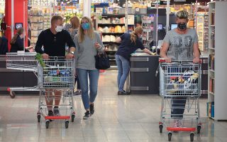 People wearing face masks leave a supermarket, after the federal state of North Rhine-Westphalia decided to make wearing protective masks obligatory in shops and public transportation to fight the spread of the coronavirus disease (COVID-19), in Bad Honnef near Bonn, Germany, April 27, 2020. REUTERS/Wolfgang Rattay